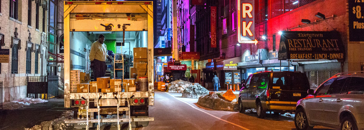 A man standing in a freight truck, unloading packages at night in a Manhattan neighborhood to conduct overnight deliveries to nearby businesses.